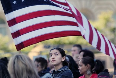 Graciela Leal, a student at Case Western Reserve University, waves a flag during a September rally at the Free Stamp in support families facing deportation. President Obama acted Friday to bring some relief to undocumented workers