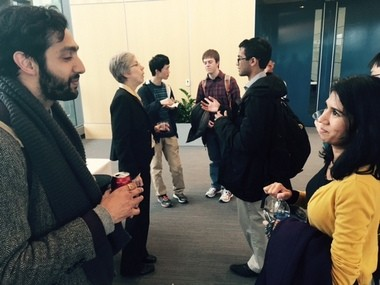 Akshai Singh, left, a graduate student working at a local environmental nonprofit, talks with Attorney Ruchi Asher, both former economics students who were once in Susan Helper's class at Case Western. Helper, the chief economist for the U.S. Department of Commerce, is in the background talking to students about manufacturing.
