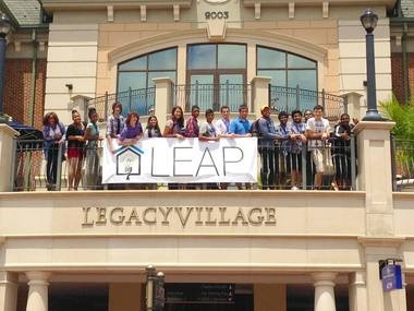 These participants in LaunchHouse's LEAP summer program for teen entrepreneurs pose with the LEAP banner at Legacy Village after completing a segment on customer development.