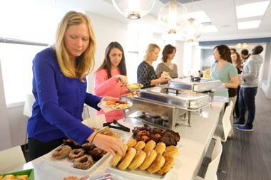 Kim Pettit, a legal assistant, left, grabs a bagel during an employee appreciation breakfast at Reminger Co. LPA law firm, on May 14, 2015.