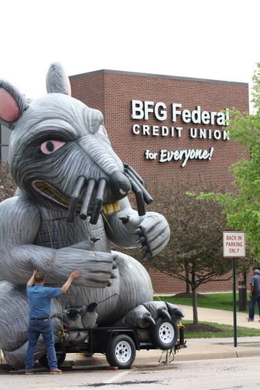 A protester positions an inflatable rat, which served as a prop, at a union rally in May in front of the BFG Federal Credit Union in Akron. Members of OPEIU Local 1794 held the rally, saying the credit union laid off workers who helped organize a union.Credit union officials say such claims are not true.