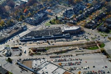 An aerial photograph shows the Shaker Plaza shopping center on Van Aken Boulevard in Shaker Heights. Van Aken Center, set to be demolished, runs along the lower edge of the image. RMS Investment Corp. plans to buy Shaker Plaza and to shift tenants there from Van Aken Center, making way for new development.