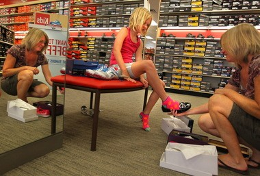 Jenna Viehland, 8, tries on shoes with her mother, Chris Viehland, at the Famous Footwear store in Fenton, Missouri, in this file photo. Clothing and shoes priced up to $75 each will be tax-free during Ohio's first Sales Tax Holiday Aug. 7-9.