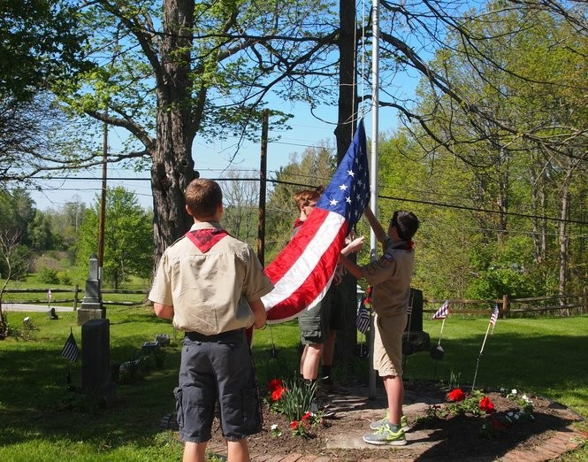 Area Boy Scouts raise the flag at Russell Township's Briar Hill Cemetery in this file photo.