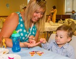 Two-year-old Charles Howley, of Gates Mills, selects a party favor decoration from those offered by his nanny, Carrie Kaczmarek, a product of the Chagrin Falls English Nanny & Governess School. The school celebrated the birth of England's Prince George