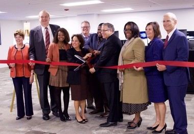 The ribbon was cut Tuesday opening the Heights-Hillcrest Communications Center in Cleveland Heights. Holding the scissors are Cuyahoga County Councilwoman Sunny Simon (center, left), Cuyahoga County Councilman Anthony Hairston, and Cuyahoga County Executive Armond Budish. The county representatives are surrounded by the mayors of the participating cities.