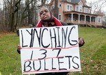 A woman protests the police-shootings of two unarmed people, killed in a hail of 137 bullets during a lengthy police chase Nov. 29, 2012.