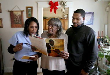 Shirley Brown, center, with daughter Leslie Brown-Hogan, left, and son Maurice Brown, Jr., right, view a funeral program for son and sibling Rodney, who died after a traffic stop with Cleveland police in 2010.