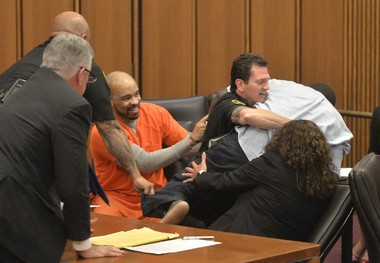 A court officer tackles Van Terry, father of one of three victims of Ohio serial killer Michael Madison, left. Terry was giving testimony about the loss of his daughter when he turned, paused and lunged toward Madison, who was grinning.