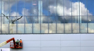 Workers assemble the ballroom wall of the Global Center for Health Innovation, formerly known as the medical mart, beneath glass panes reflecting the August sky last summer. This wall looks north at Lake Erie, the Science Center, and Browns Stadium.