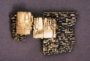 "The 1982 ""Black and Gold Pendant Brooch"" by John Paul Miller exemplifies the goldsmith's late style."