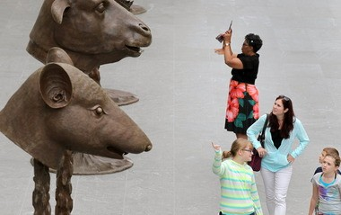 Viewers interact with Ai Weiwei's installation of monumental bronze sculptures of Chinese zodiac creatures at the Cleveland Museum of Art.