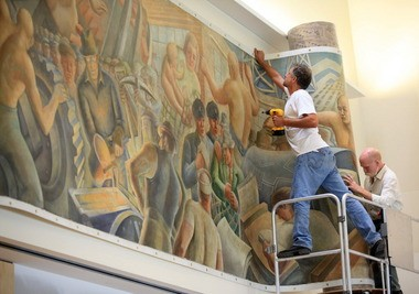 Chris Pelrine, left, and O5, employees of ICA Art Conservation, install one of two Elmer Brown murals at Cleveland State University in 2010. Brown originally painted the works for Valleyview Homes in 1940 as a WPA art project.