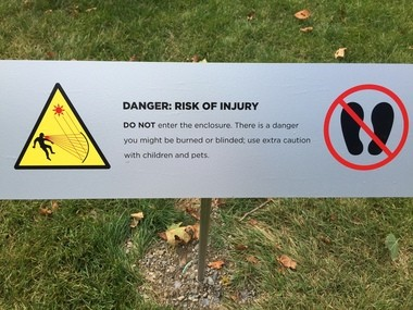 """A warning sign with an alarming graphic is part of the installation of Anish Kapoor's """"C-Curve"""" at the Cleveland Museum of Art."""