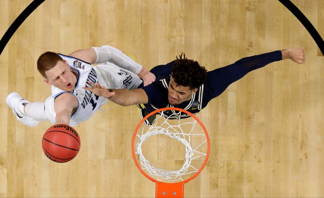 Villanova guard Donte DiVincenzo, left, drives to the basket past Michigan forward Isaiah Livers during the first half of the championship game Monday, April 2.