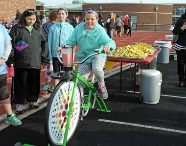 A student takes her turn on the Fender Blender bicycle during a recent elementary school fundraiser at Fairview Stadium.