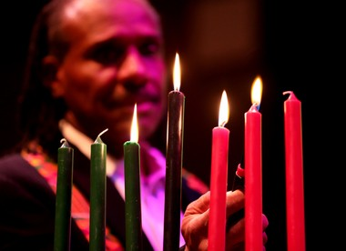 Akil Marshall lights a candle to celebrate the fourth day of Kwanzaa.