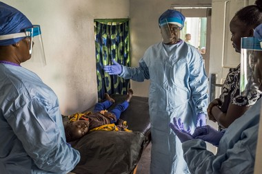 Nurses discuss a young patient in a newly-built screening area at Logan Town, a clinic in Monrovia, Liberia, Feb. 18, 2015. As the Ebola outbreak started nearly a year ago, Logan Town's workers saw patients by candlelight and washed their hands in buckets. (Daniel Berehulak/The New York Times)