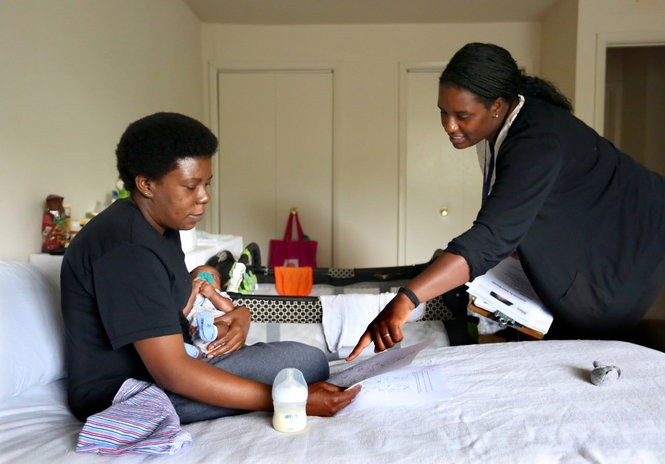 Home visitor Celeste Spears explains infant massage to 36-year-old Njkema Smith.