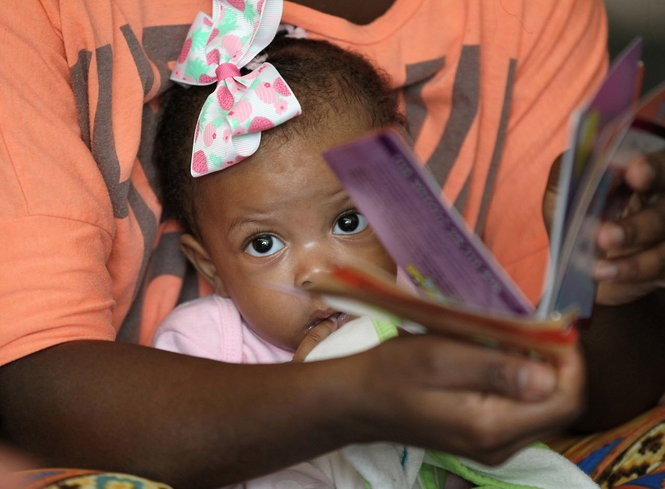 No child is too young for books, B'More staff teach. Chloe Turner, 5 months, may not understand, but hearing new words is critical for her growing brain. (Lisa DeJong/The Plain Dealer)