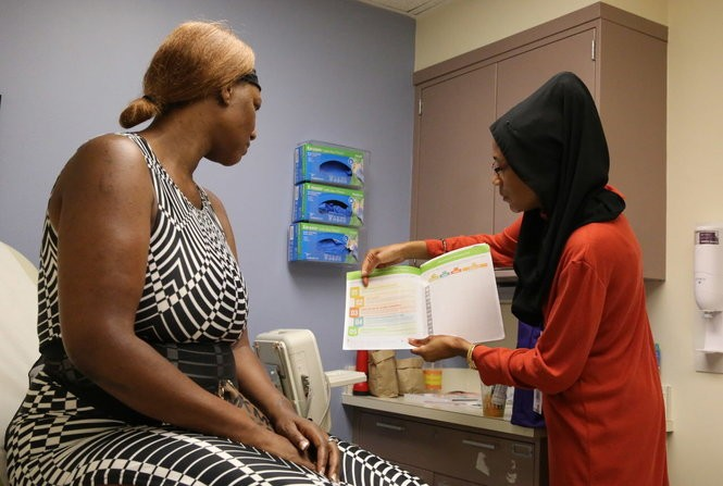 Doula Myranda Majid, right, of Birthing Beautiful Communities, discusses meal planning with expectant mother LE Tisha Hopkins during a pregnancy checkup at University Hospitals Rainbow Babies & Children's Hospital.