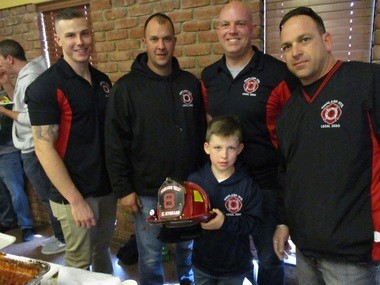 Representing the Highland Heights Fire Department were, from left, firefighters Bob Tyler and Bryon Barna, Lt. Bill Bernhard, and firefighter Bob Tagg. Holding the helmet is Tagg's son, Dominic, 7.