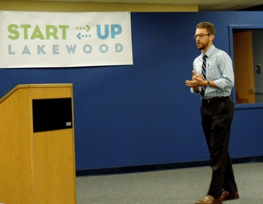 Bryce Sylvester, Lakewood city planner, explains the evening's proceedings to the finalists at University of Akron Lakewood Aug. 26.