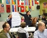 Audience members display the questions formulated at their table regarding the future of the schools.