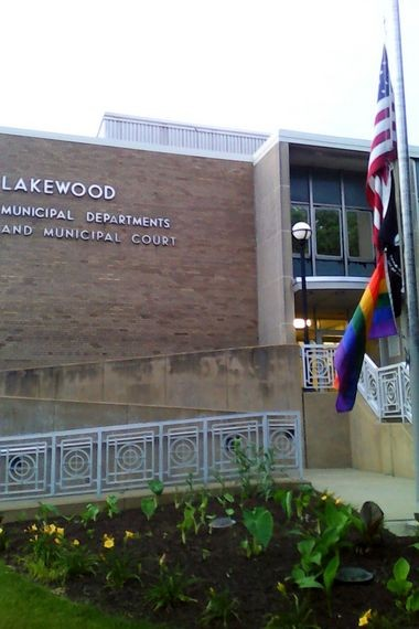 The American flag and the rainbow flag fly at half-mast in front of Lakewood City Hall Monday.