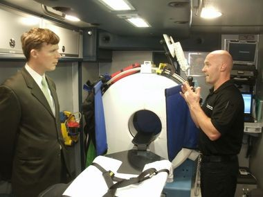 Cleveland Clinic CT technician Josh Carnes, right, tells City Councilman Tom Bullock how the mobile CT unit works.
