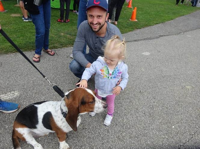 """Lakewood resident Raeani Guzik, 1 1/2 , gets acquainted with Huckleberry """"Huck"""" Bixenstine, a 3-year-old bassett hound who was at the festival with his owners, Matt Bixenstine and family. Raeani's dad, Jared, keeps an eye on things."""