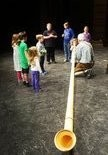 Jim Esswein helps youngsters learn the proper technique for the Alphorn.
