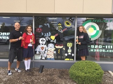 Student-artists Mia Polisena and Sammi Fedeli with their Superhero Monsters outside Health 360 in Mayfield Village. They won 2nd place.