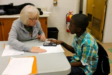 ACE program co-founder Carol Andregg, a retired teacher, makes sure Claggett Middle School sixth-grader Angelo Williams gets some hands-on experience with his calculator while the two were working on Angelo's math homework.