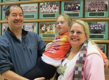 Bill and Stacey Memberg carry their energetic daughter Sarah on their shoulders. The family was at a Medina School Board meeting to describe how the Sparkle Effect program was helping the community and the students practice inclusiveness.
