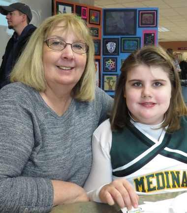 Kathy Lee, left, and her granddaughter Fiona Moore, attended an art show and pancake breakfast in support of Medina City Schools. Fiona is wearing the uniform of her cheering team, the Sparkles.