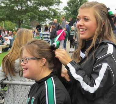 Hornet Sparkle cheering squad member, Claire Nehrenz, left, lets her buddy Miranda Paich get her ready to cheer on the sidelines at a Highland football home game.