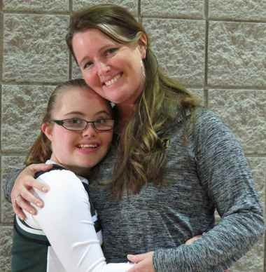 Bre Jackson, left, wearing the uniform of her Sparkle cheering squad, shares a hug with varsity cheerleading coach, Wendi Clardy. The two were attending a student art and talent show at the school in January where the Sparkles performed a routine on the stage.
