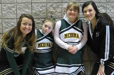 Medina Sparkles Sarah Memberg and Erin Hawley, center, are flanked by varsity cheerleaders Dayna Maier, far left, and Nikki Sherman as they show school spirit by sporting their cheerleading uniforms during a recent community breakfast and art show.