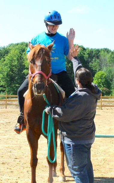Chris Milota and Crystal VanNewkirk share a high-five after Chris completed the obstacle course in the outdoor arena at Medina Creative Therapy Ranch.