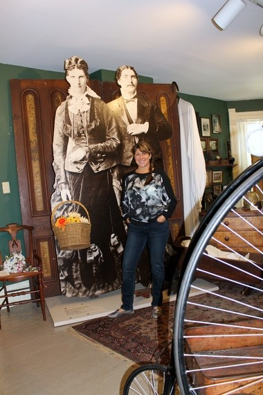 Katie Palmer, who has revamped all of the display rooms at the John Smart House museum in Medina, stands in front of the giants of Seville, who feature prominently in an exhibit on the second floor.