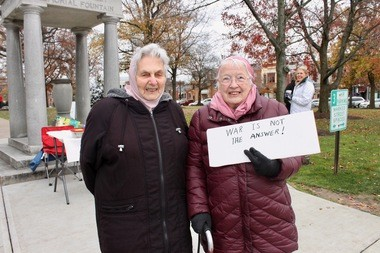 """Mary Ellen Coolman, 89, left and her """"older"""" friend, Adele Looney, were among those gathered on the Medina Square yesterday to stand in solidarity with people who feel disenfranchised by American democracy. Both women are Quakers and activists for social justice."""