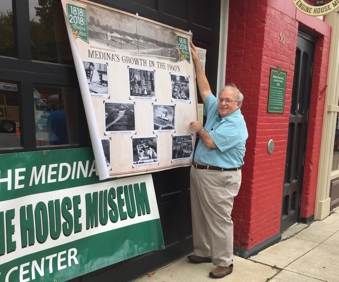 Roger Smalley, director of the Town Hall and Engine House Museum, hangs an historical banner on the front of the museum on the south side of Medina's Public Square during this weekend's Medina Fest. (Mary Jane Brewer, special to cleveland.com)