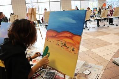 Sophomore Mia Vela adding cacti to the foreground of her desert scene.