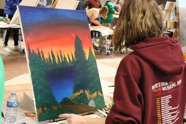 """Sophomore Corrine Lecian painting """"happy little trees"""" like her inspiration for her painting, Bob Ross."""