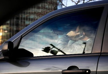 See what this driver is doing, kids? Don't do it or you could lose your driver's license under a state statute that begins being enforced today on drivers younger than 18. A hands-free phone isn't permitted under the new law, either.