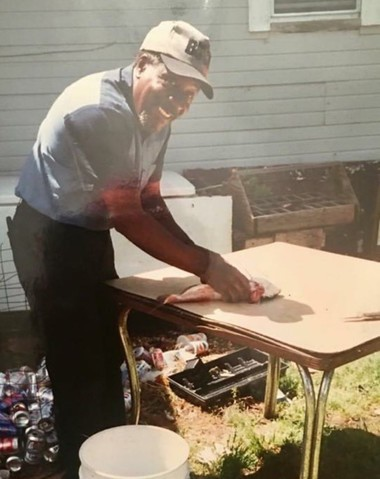 Robert Godwin Sr. cleaning his catch, in an undated family photo shared by daughter Brenda Godwin-Joiner. The photo was printed on the cover of his funeral program.