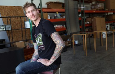 Jason Radcliffe sits on a stool of his own making. It features a raw wood seat and raw steel supports.