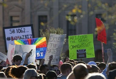 Opponents of a religious freedom bill approved last week by Arizona legislators urge Gov. Brewer to veto the bill during a protest rally Friday at the state Capitol in Phoenix.
