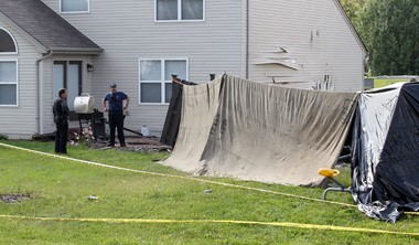 Caution tape stretches out at the back of a house, Saturday, Sept. 20, 2014, on Brightfield Court, in Liberty Township, Ohio, where a plane crashed.